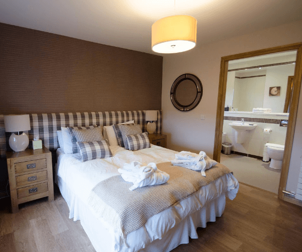 Large sized bed with white bedding with ensuite bathroom