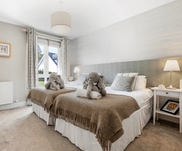 Two double beds in light grey painted bedroom