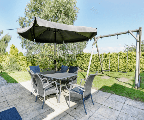 Large garden full of greenery and outside seating with parasol