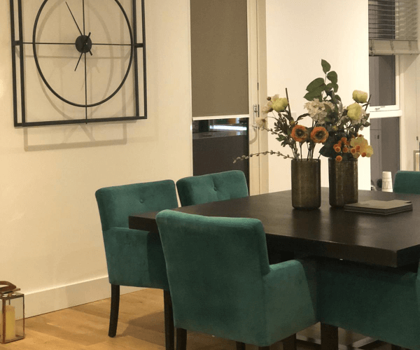 Dark wood dining table with green dining seats