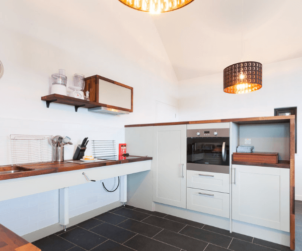 White kitchen with bronze worktops and built in oven