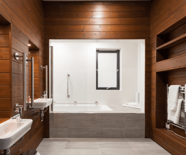 Bathroom with bath tub and sinks with built in handrails for disability support