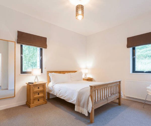 Bedroom with large bed and 2 small windows
