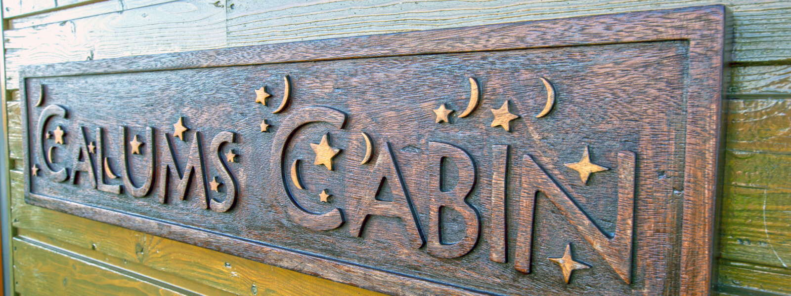 Wooden sign on wall that has Calums Cabin logo engraved into it.
