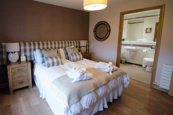 Queen sized bed with striped bedding in large room with wooden flooring and en suite bathroom